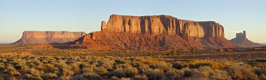 Flat Mesas at Dawn. Two flat mesas and a vertical one are sailing through the Monument Valley at cold November dawn, showing off the sediment layers from Stock Photos