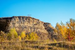 Flat mountain rock on the background of a blue sky and with autumn trees at the foot_. Flat mountain rock on the background of a blue sky and with autumn trees stock photo