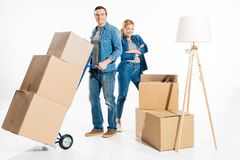 Flat moving concept with woman and man carrying cardboard boxes on delivery cart stock photos