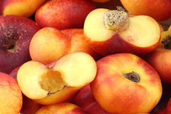 Flat nectarines and a cut one Royalty Free Stock Photos