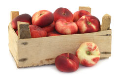 Flat nectarines in a wooden crate Royalty Free Stock Images