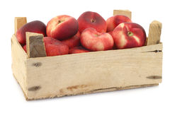 Flat nectarines in a wooden crate Royalty Free Stock Photos