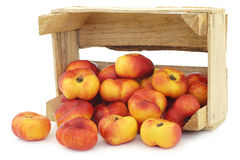 Flat nectarines in a wooden crate Stock Image