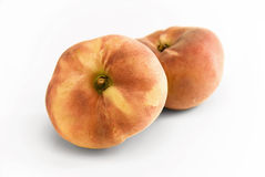 Flat Peaches. Two flat Peaches lying together on white background royalty free stock images