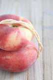 Flat peaches. Two flat peaches on a table Royalty Free Stock Image