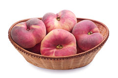 Flat peaches in wicker basket Stock Photo
