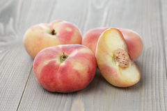 Flat peaches on wood table Stock Images