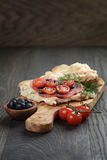 Flat pita bread with salami and vegetables on wood Stock Photo