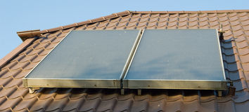 Flat-plate solar collector. On metal red roof Stock Photos