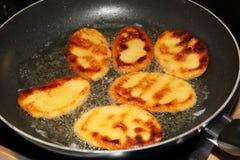 Flat potato dumplings roasting in hot oil Stock Photo