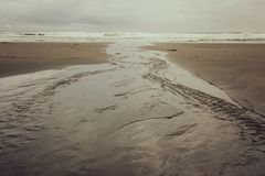 A Flat River Winds its way toward the Sea. A smooth flat river meanders towards the sea on New Zealand`s West Coast Piha Beach, a favourite for surfers royalty free stock photo