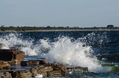 Flat rock coast with splashing water Stock Photo