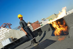 Flat roof covering repair works with roofing felt. Roofer installing Roofing felt with heating and melting of bitumen roll by torch on flame during roof repair Royalty Free Stock Image