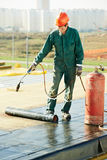Flat roof covering repair works with roofing felt. Roofer installing Roofing felt with heating and melting of bitumen roll by torch on flame during roof repair Royalty Free Stock Images