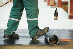 Flat roof covering repair works with roofing felt. Roofer installing Roofing felt with heating and melting of bitumen roll by torch on flame during roof repair Stock Images