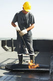 Flat roof covering repair works with roofing felt. Roofer installing Roofing felt with heating and melting of bitumen roll by torch on flame during roof repair Stock Photography