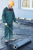 Flat roof covering repair works with roofing felt Stock Images