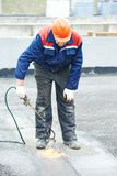 Flat roof covering repair works with roofing felt Royalty Free Stock Photography