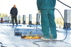 Flat roof covering repair works with roofing felt Stock Photos