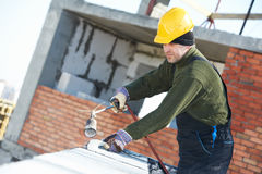 Flat roof covering works with roofing felt. Roofer installing Roofing felt with heating and melting roll of bitumen roll by torch on flame Royalty Free Stock Images