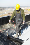 Flat roof covering works with roofing felt. Roofer installing Roofing felt with heating and melting roll of bitumen roll by torch on flame Stock Photography