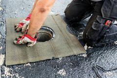 Flat roof installation. Heating and melting bitumen roofing felt.  royalty free stock image