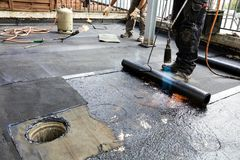 Flat roof installation. Heating and melting bitumen roofing felt.  royalty free stock photos