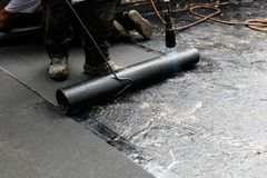 Flat roof installation. Heating and melting bitumen roofing felt royalty free stock photos