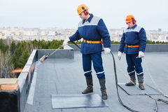 Flat roof installation. Heating and melting bitumen roofing felt. Flat roof installation. builders workers heating, melting and applying bitumen roofing felt by stock photography