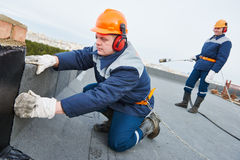 Flat roof installation. Heating and melting bitumen roofing felt Royalty Free Stock Photo