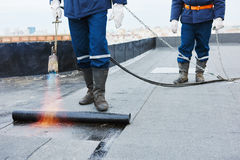 Flat roof installation. Heating and melting bitumen roofing felt. By flame torch at construction site stock image
