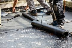 Flat roof installation. Heating and melting bitumen roofing felt.  stock image