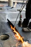 Flat roof installation. Heating and melting bitumen roofing felt.  stock photography