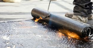 Flat roof installation. Heating and melting bitumen roofing felt stock images