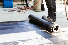 Flat roof installation. Heating and melting bitumen roofing felt.  stock photos