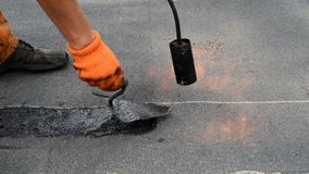 Flat roof repair. Roofer heating burner flame brushes layer shale coating from the end of the roll of waterproofing to improve adhesion when surfacing next roll stock footage