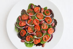 Flat salad of cherry tomatoes, kalamata olives, red onion, and mangold leafs dressed with olive oil, lemon juice and finly chopped Stock Photo