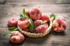 Flat saturn peaches. On the wooden table Stock Photos
