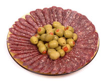 Flat sausage. In plate garnished with olives on a white background Royalty Free Stock Image