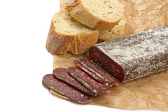 Flat sausage. Sliced flat sausage and bread on paper Stock Image
