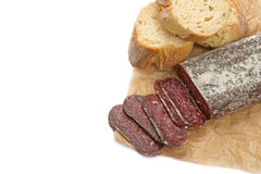 Flat sausage. Sliced flat sausage and bread on paper Royalty Free Stock Image