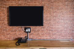 Flat screen television on a brick wall. Flat screen television hanging at the brick wall with copy space in living room or bedroom Stock Photo