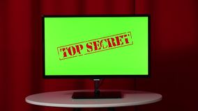 Flat screen TV. Standing on a white table. Green screen. Top secret. Red background.