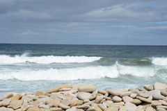 Flat sea worn pebbles and crashing waves Stock Image