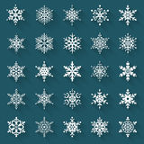 Flat snowflakes. Vector icons set. Flat snowflakes. Icons isolated on a blue background. Set of 25 white symbols with long shadows. Elements of various shape Stock Images