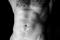 Flat sporty male belly. Closeup black and white photo on dark background Royalty Free Stock Photography