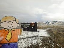 Flat Stanley doll at Yellowstone Natioal Park sign at entrance i Royalty Free Stock Image