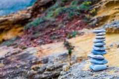 Flat stones stacked zen-like at a colorful rockface royalty free stock photos