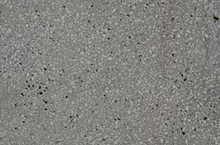 Gray textured flat surface of the artificial stone block. Flat surface of artificial stone made of mixture of mortar and small marble pieces. Gray spotted stone stock image