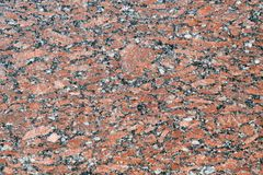 The flat surface of a natural marble or brown granite slab. On the surface there are many small cracks, streaks, stripes and dots. Background, Wallpaper or royalty free stock photos